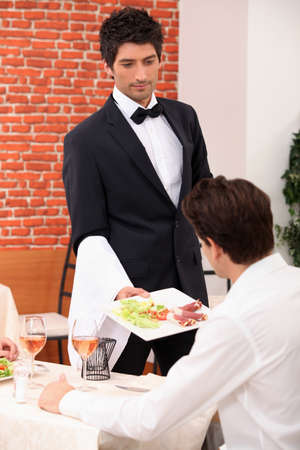 serving: Waiter serving a meal in a restaurant Stock Photo