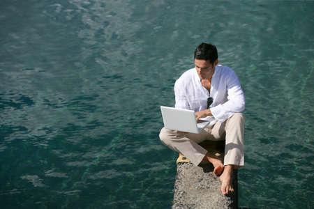 hombre solitario: Hombre en un pontón que usa el ordenador Foto de archivo