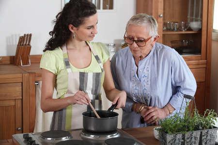 one senior adult woman: Cocina joven, mujer, de una anciana