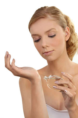 perfumer: dainty young blonde putting on perfume