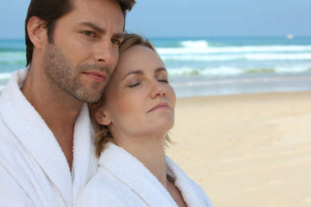 bath gown: Husband and wife on the beach in bath robes Stock Photo