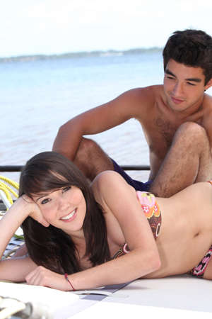 Young couple sunbathing on board a catamaran photo