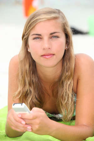 A young woman texting on the beach. photo