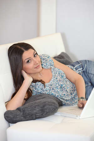 everywhere: brunette lolling in sofa Stock Photo