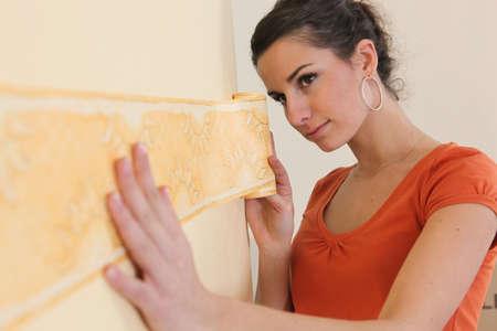 Woman putting up  wallpaper border photo