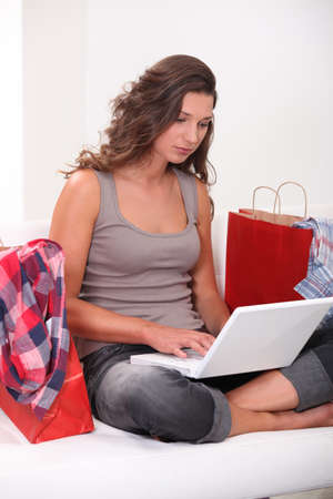 e marketing: Woman at home shopping on-line surrounded by shopping bags