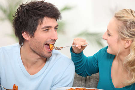 Woman feeding her husband food photo
