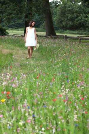 Summery woman walking through a pretty wild flower meadow photo