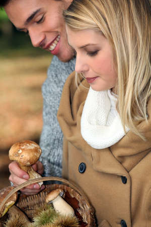Young couple gathering wild mushrooms photo