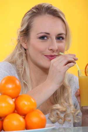 swallowing: Woman drinking a glass of orange juice with a straw Stock Photo