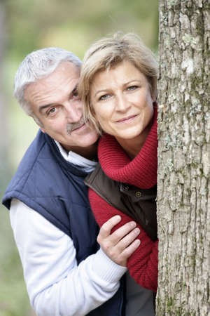 Older couple peeking around a tree photo