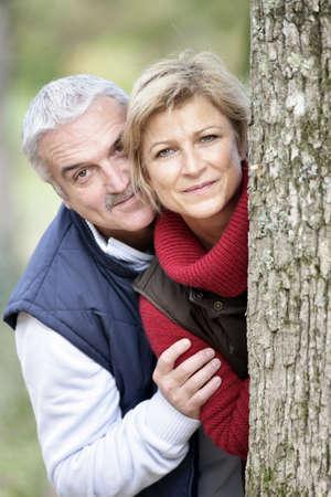 Older couple peeking around a tree Stock Photo - 11293724