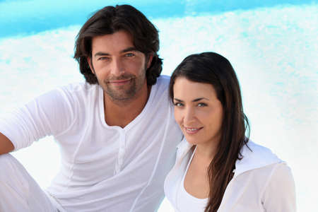 Couple wearing white clothing sat by swimming pool photo
