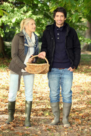 wellies: Couple collecting chestnuts