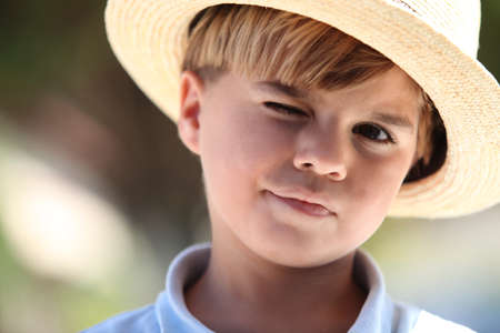 boater: Closeup of a young boy in a straw hat Stock Photo