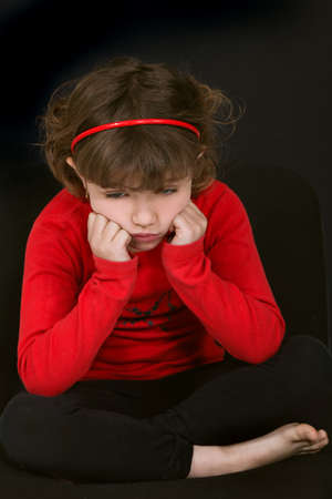 decepción: niña haciendo un mohín con la cara apoyada en las manos contra el fondo negro