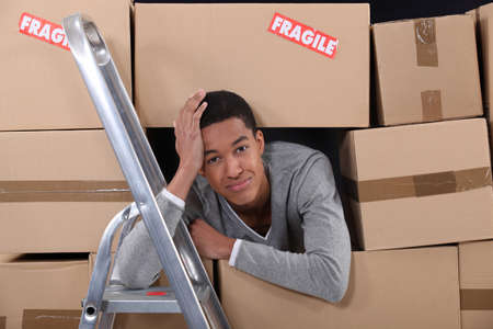 first time buyer: young man surrounded by boxes moving into a new apartment Stock Photo
