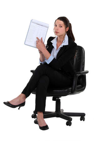 20 s: Woman sitting on chair pointing at clipboard
