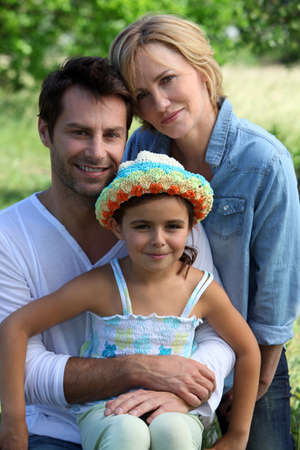 close knit: Parents and young daughter in the garden on a summer day Stock Photo