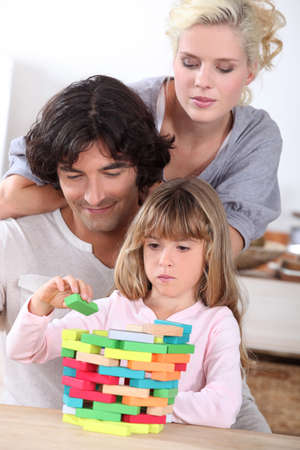 Parents building blocks with their daughter photo