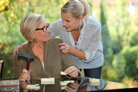 old carer: a young blonde woman touching shoulders of an old blonde woman taking a crutch in her hand Stock Photo
