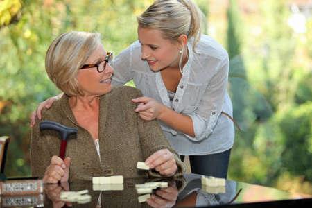 una mujer rubia joven tocando los hombros de una mujer mayor rubia de tomar una muleta en la mano Foto de archivo