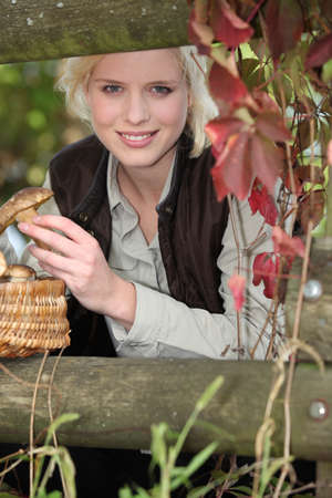 beautiful woman gathering mushrooms in the park photo