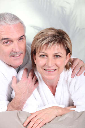 intimacy: Mature couple in bathrobe laid on a bed