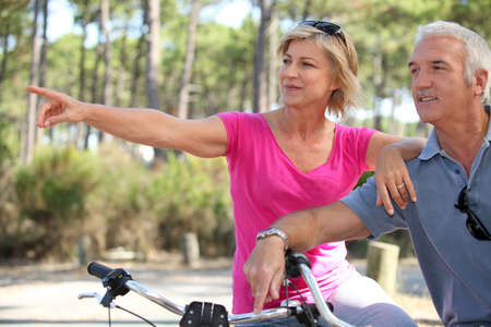 senior couple riding bikes in the park photo
