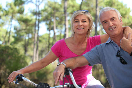 55 59 years: Older couple riding bikes in the countryside Stock Photo
