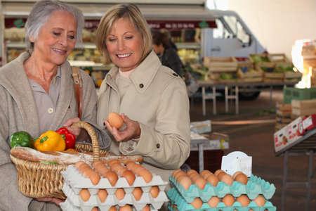 two senior women shopping on the market photo