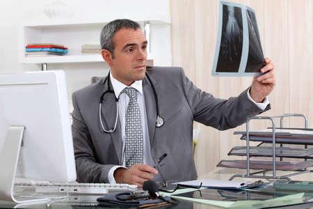 trained nurse: Doctor examining x-ray of hand Stock Photo