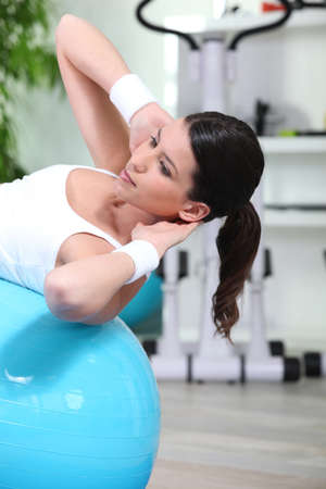 Woman doing sit-ups on gym ball photo