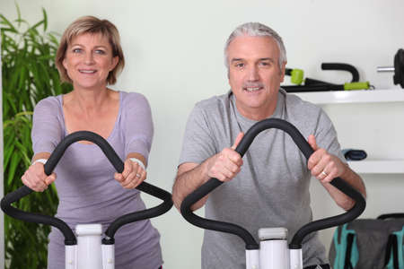 senior couple riding bikes in the gym photo