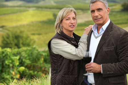 40 year old woman: Couple drinking a glass of wine in a vineyard Stock Photo