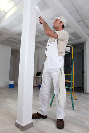 Tradesman painting a column photo