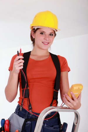 ohm: Female electrician using a voltmeter