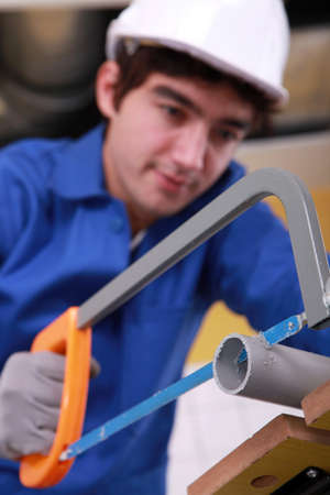 jumpsuite: young man is cutting a pvc pipe with a saw Stock Photo