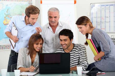 profesores: Los estudiantes que muestran a la maestra de v�deo en el ordenador port�til