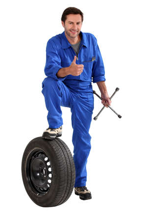 Studio shot of a mechanic with tyre and wrench, giving a thumbs up photo