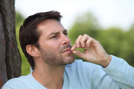 40 45: Man chewing on a piece of grass Stock Photo