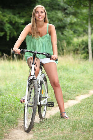 16 19 years: Young woman on a bike in the countryside