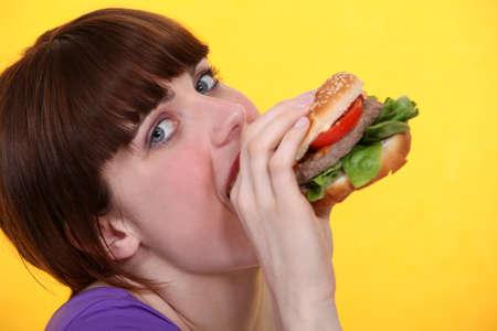 Woman eating a hamburger photo