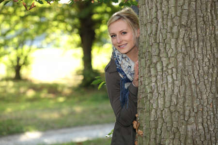 hide: Woman hiding behind a tree