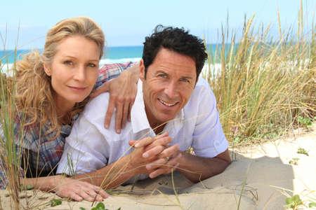 man 40 50: Couple lying on the sand.