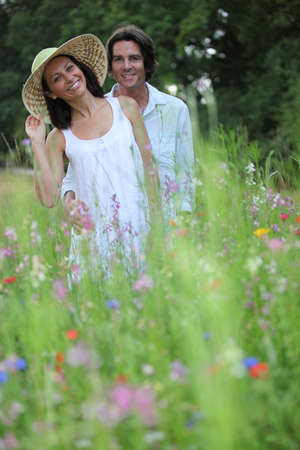 happy young couple in high grass amid wild flowers photo