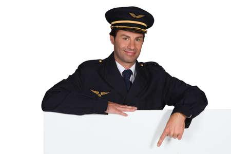 military man: Pilot pointing at advertising board