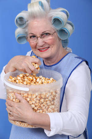 curlers: senior woman with curlers on her head eating popcorn Stock Photo