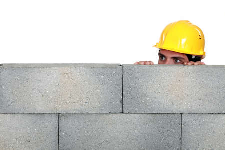snooping: craftsman hiding behind a stone wall Stock Photo