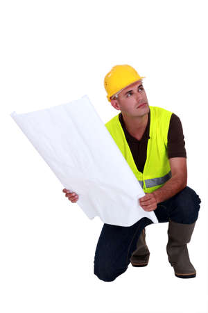 practiced: construction supervisor holding a blueprint